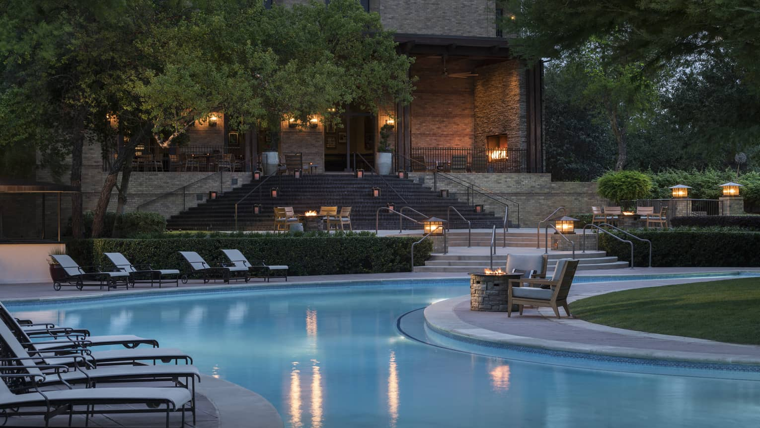 Fire pits, lanterns, lounge chairs around outdoor swimming pool at dusk