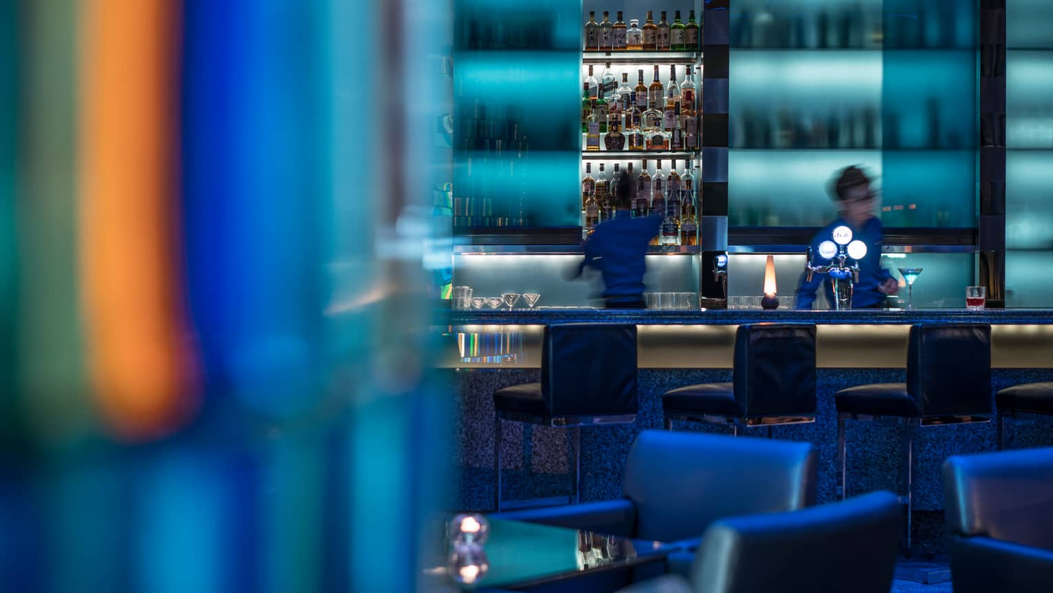 Bartenders behind illuminated blue bar, stools, colourful lights