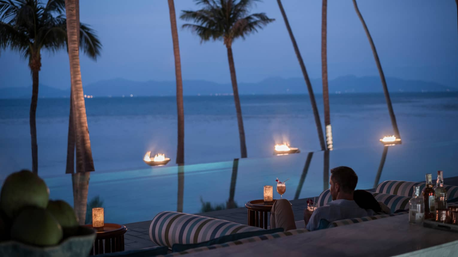 Guests sit outside CoCoRum enjoying drinks by the infinity pool with views of the Gulf of Thailand