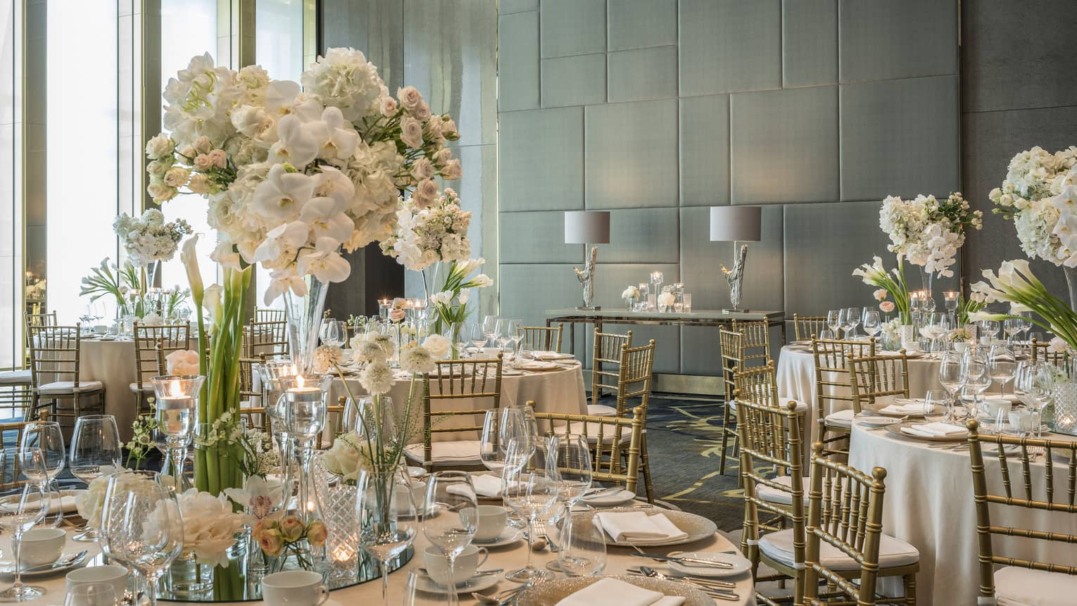 The tables of a wedding reception are set with white tall florals, clear glassware, white plates and silver tableware