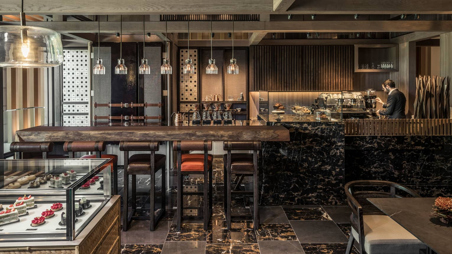 The Lounge rustic wood and black marble bar lined with leather stools, glass display with desserts