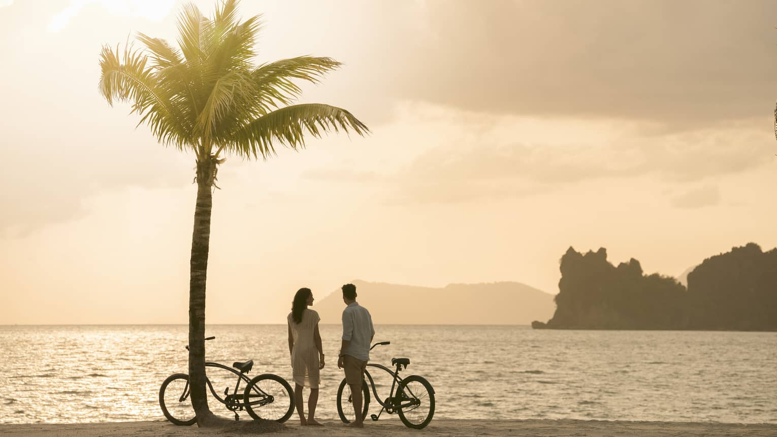 A man and woman on the beach at sunset with bikes