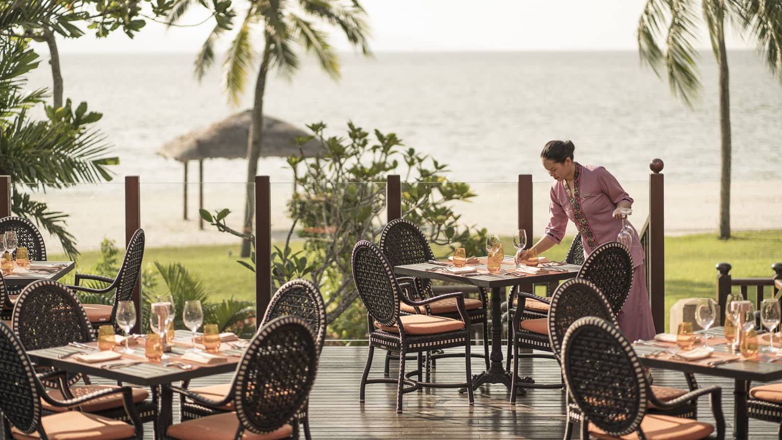 A server at Ikan Ikan sets a table on the outdoor terrace overlooking the beach