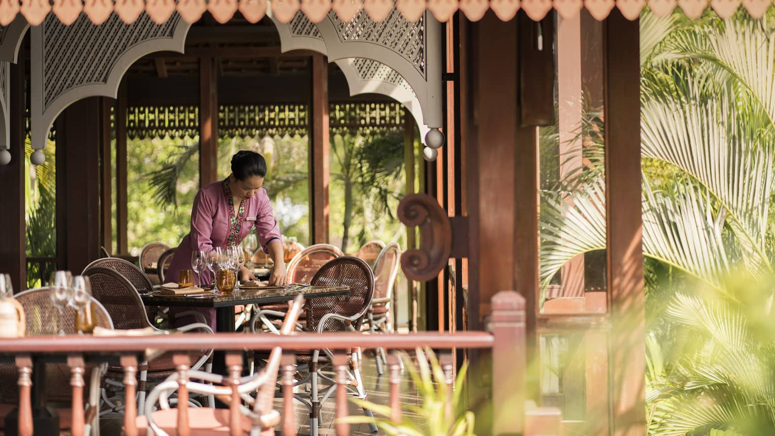 A Four Seasons staff setting the table in the open-aired Ikan Ikan at Four Seasons Langkawi