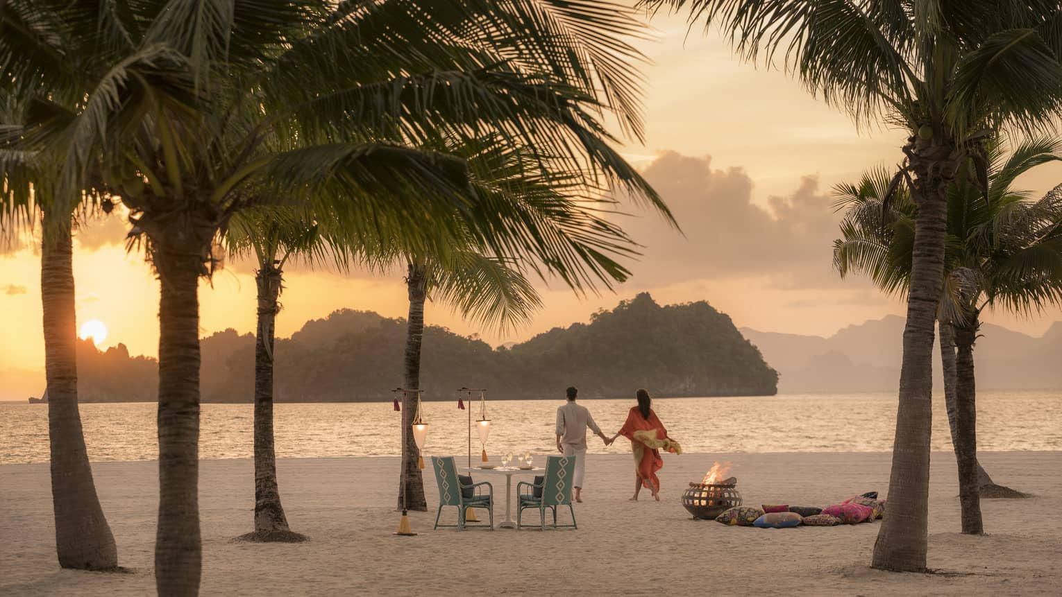 A man and woman on a beach having a Punta chintai private dinner at Four Seasons Langkawi