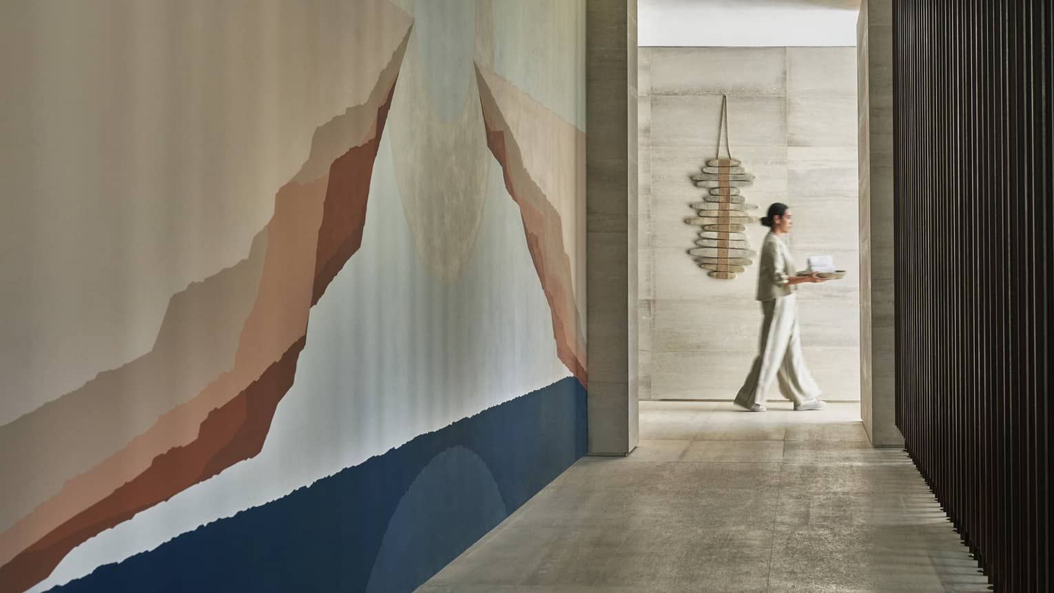 A four seasons spa staff carries a tray through a white marble corridor