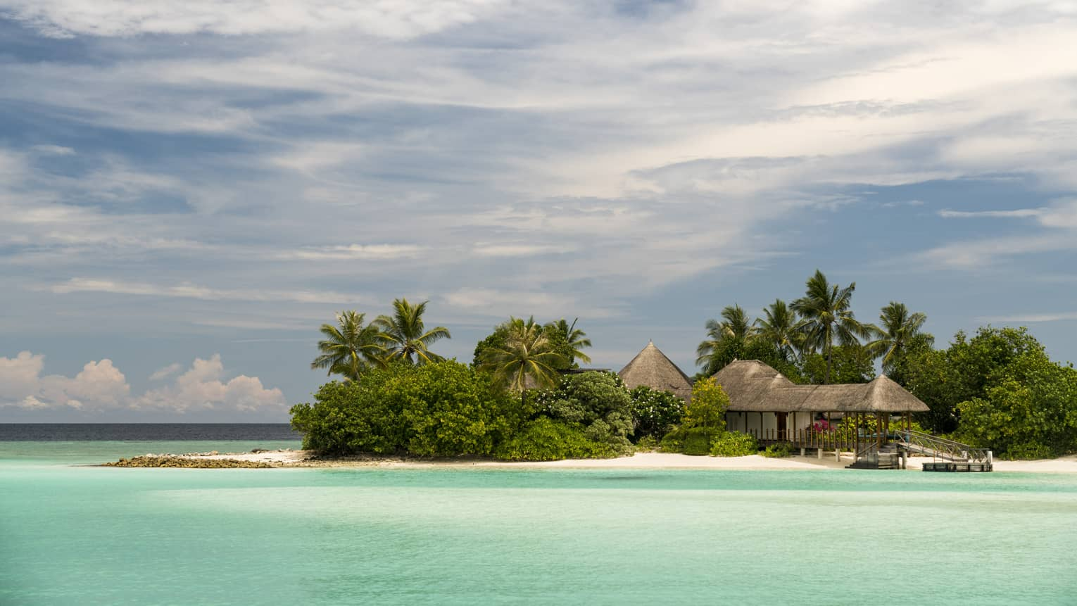 Small island with thatched-roof building housing The Island Spa, surrounded by turquoise waters