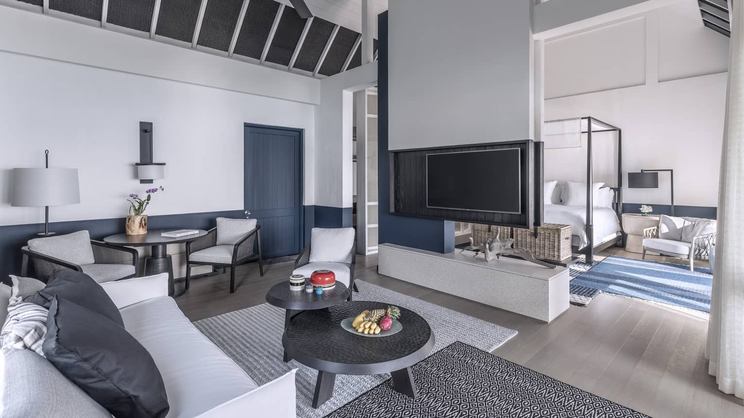 A brightly lit, cozy living room with a television, couch and access to the bedroom