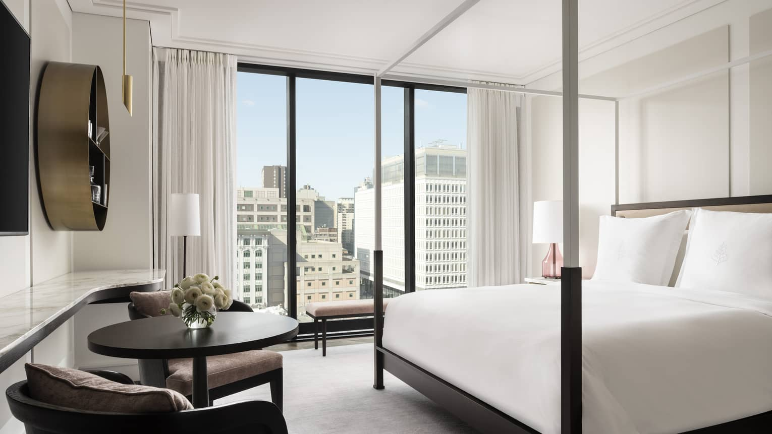 Superior King Room with modern four-poster bed in all-white room with conversation vignette and floor-to-ceiling windows with city views