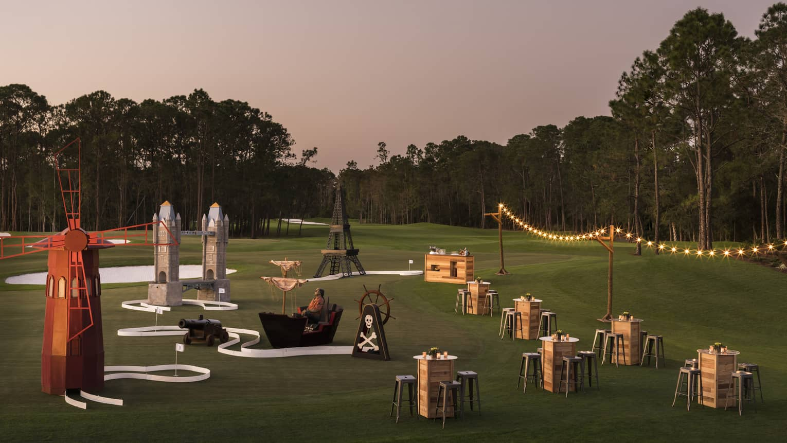 The sun sets over a golf course that's set up with stringed lights and cocktail tables for a putt putt event