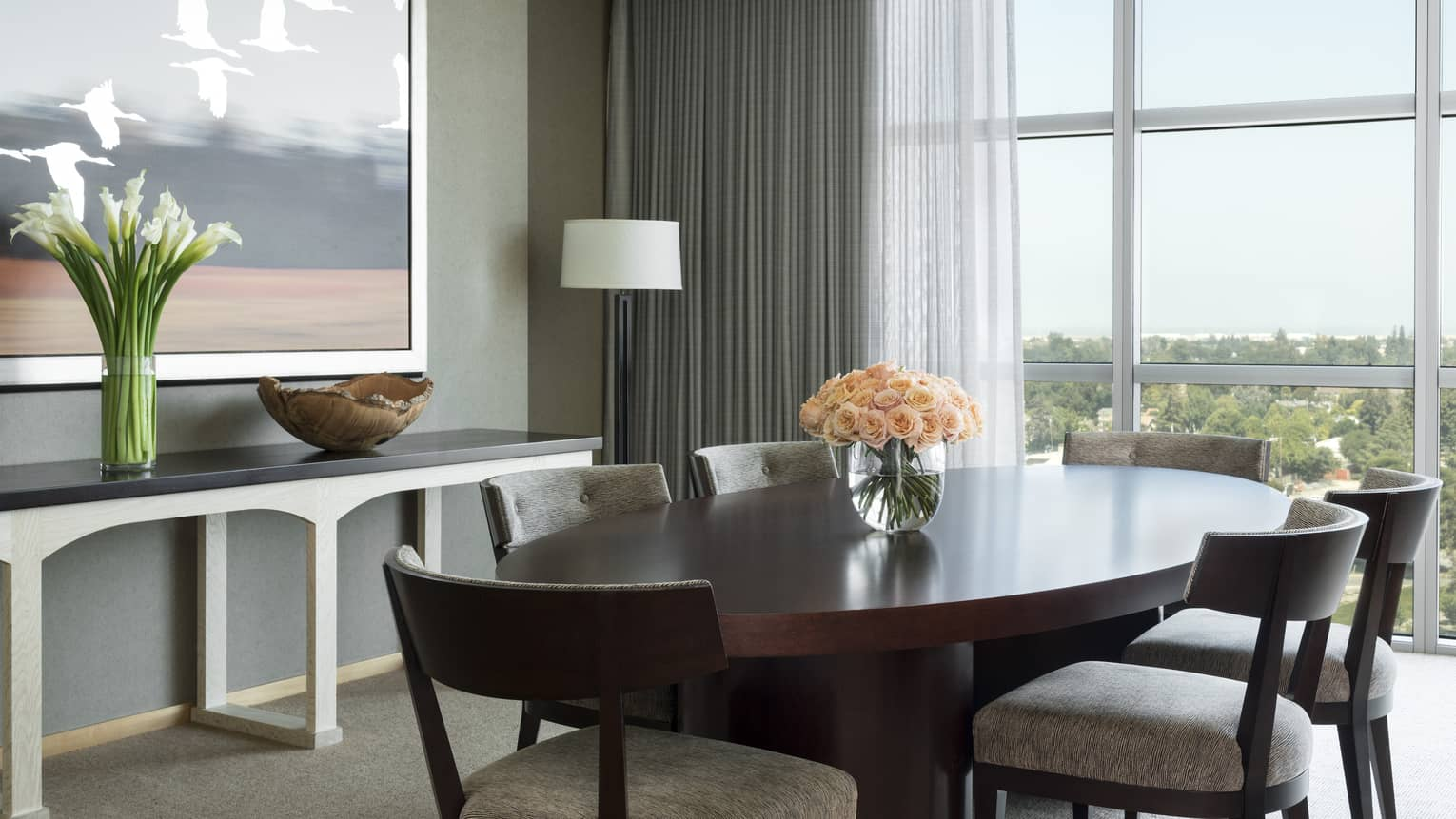 Presidential Suite round dining table, console and painting by floor-to-ceiling window