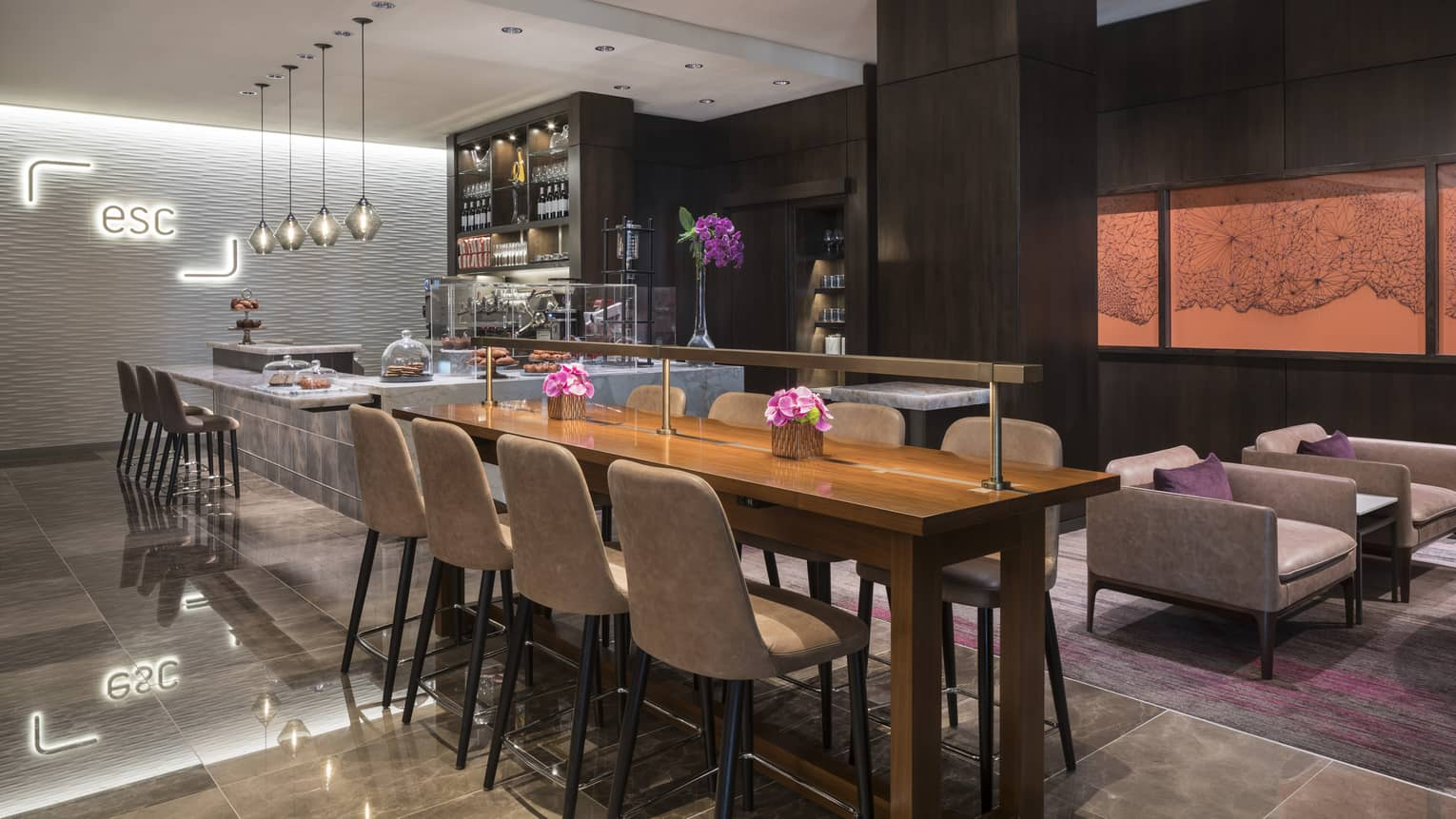 Dining room with long communal table, stone and marble bar, modern light, sign