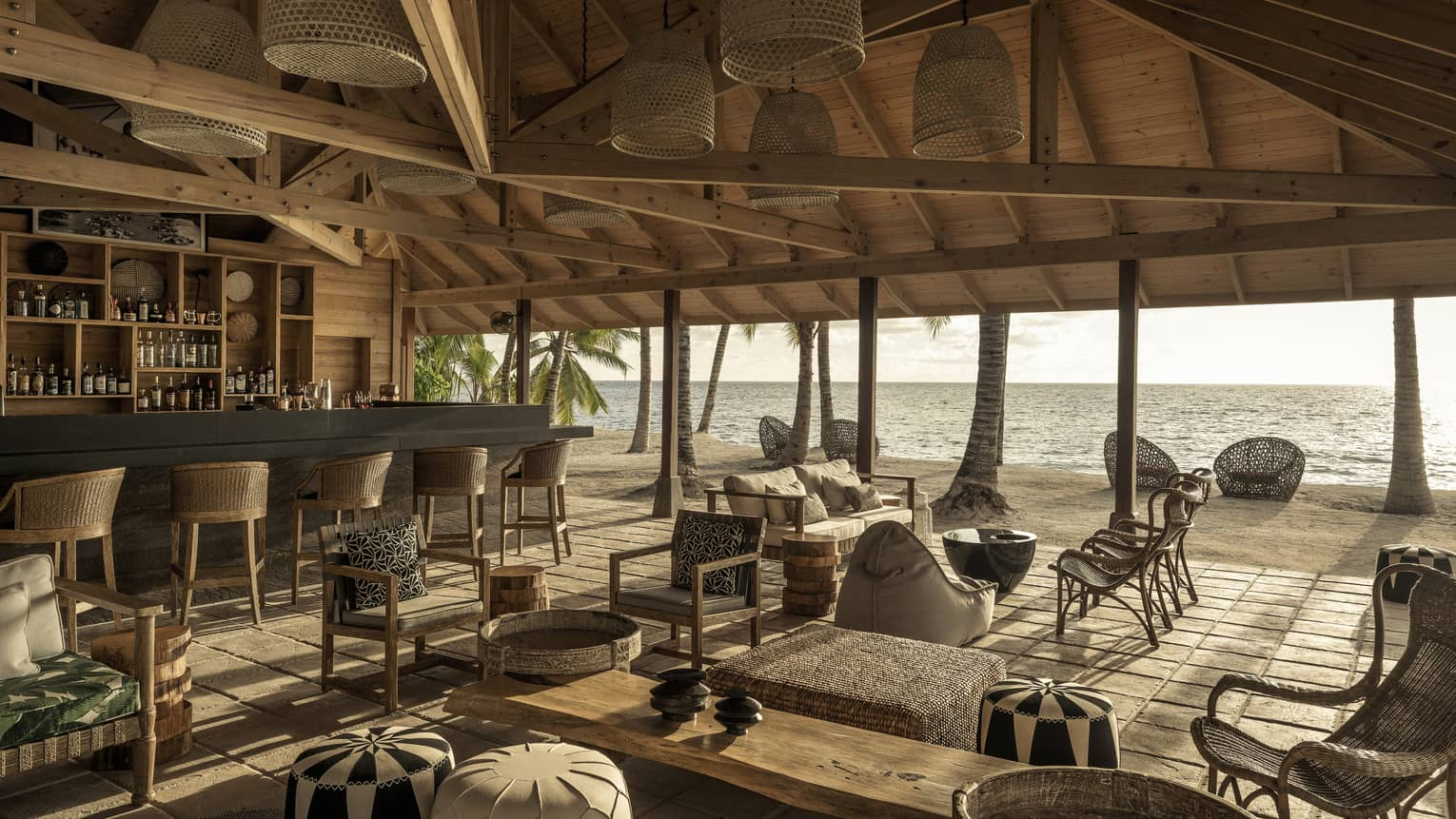 Bar with bar stools and lounge with grouped seating under vaulted wooden ceiling with open-air view of beach and ocean