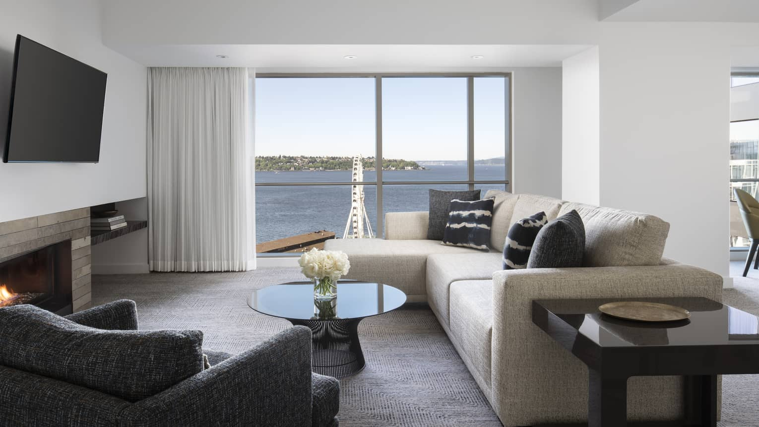 The Deluxe Elliot Bay Suite living room has comfortable couches and a view of the Seattle Great Wheel