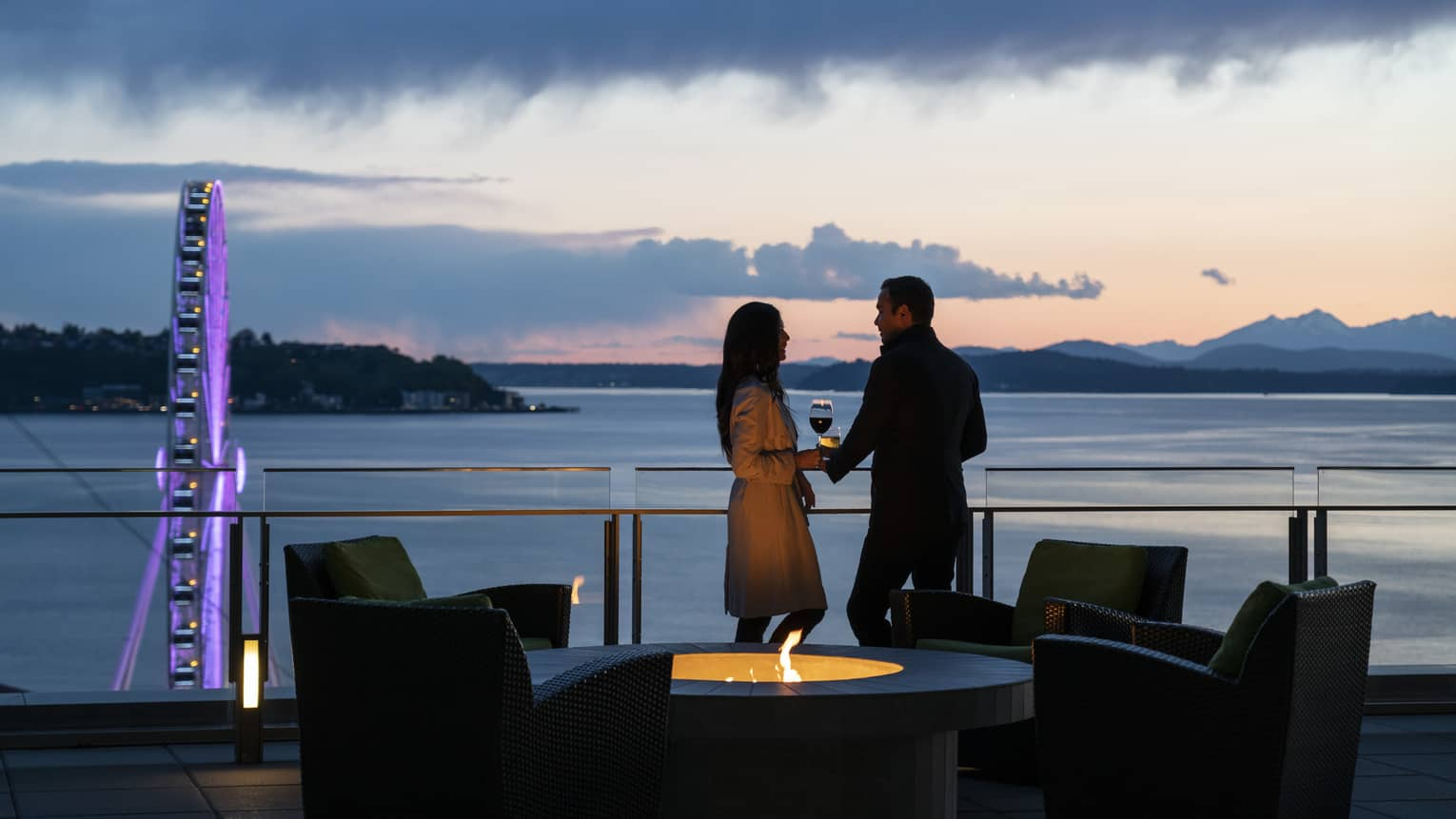 A couple holds hands and shares wine on the balcony as the sun sets