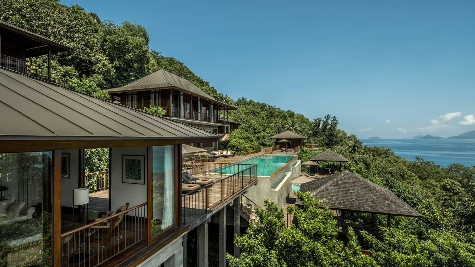 Four-Bedroom Residence Villa roofs, patios amid trees on mountain, ocean below
