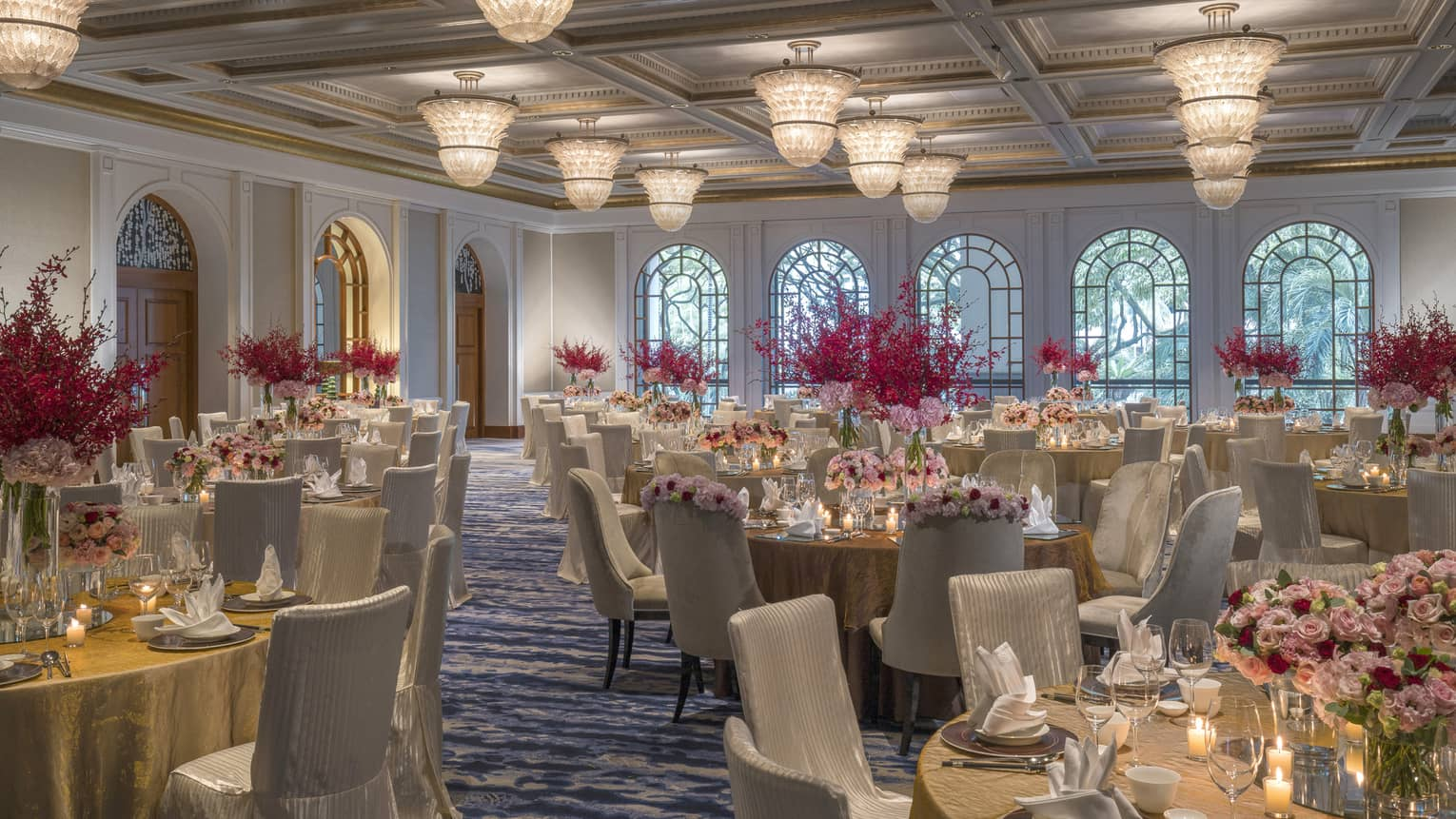 Circular tables are set for a meal and decorated with candles and pink and red bouquets