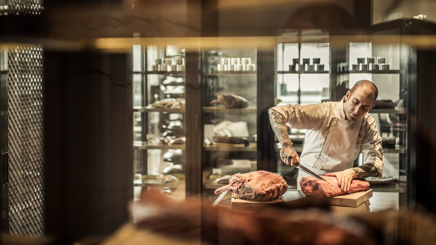 Chef in uniform with tattoos on arm carves large piece of raw meat on butcher's block