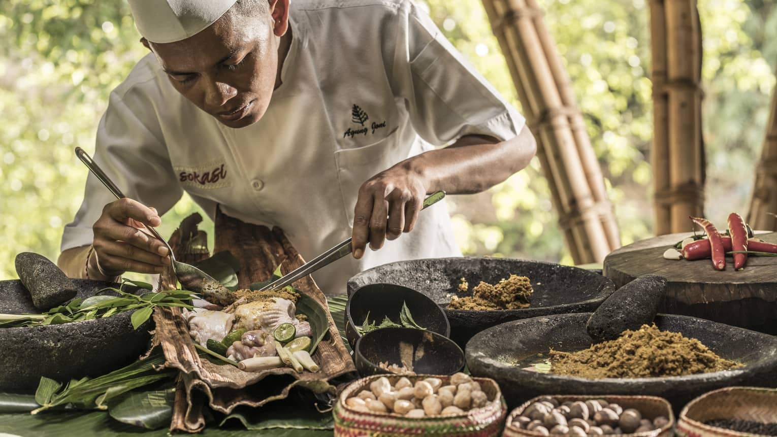 Chef Suta preparing a meal with meat, nuts, vegetables and spices in Bali