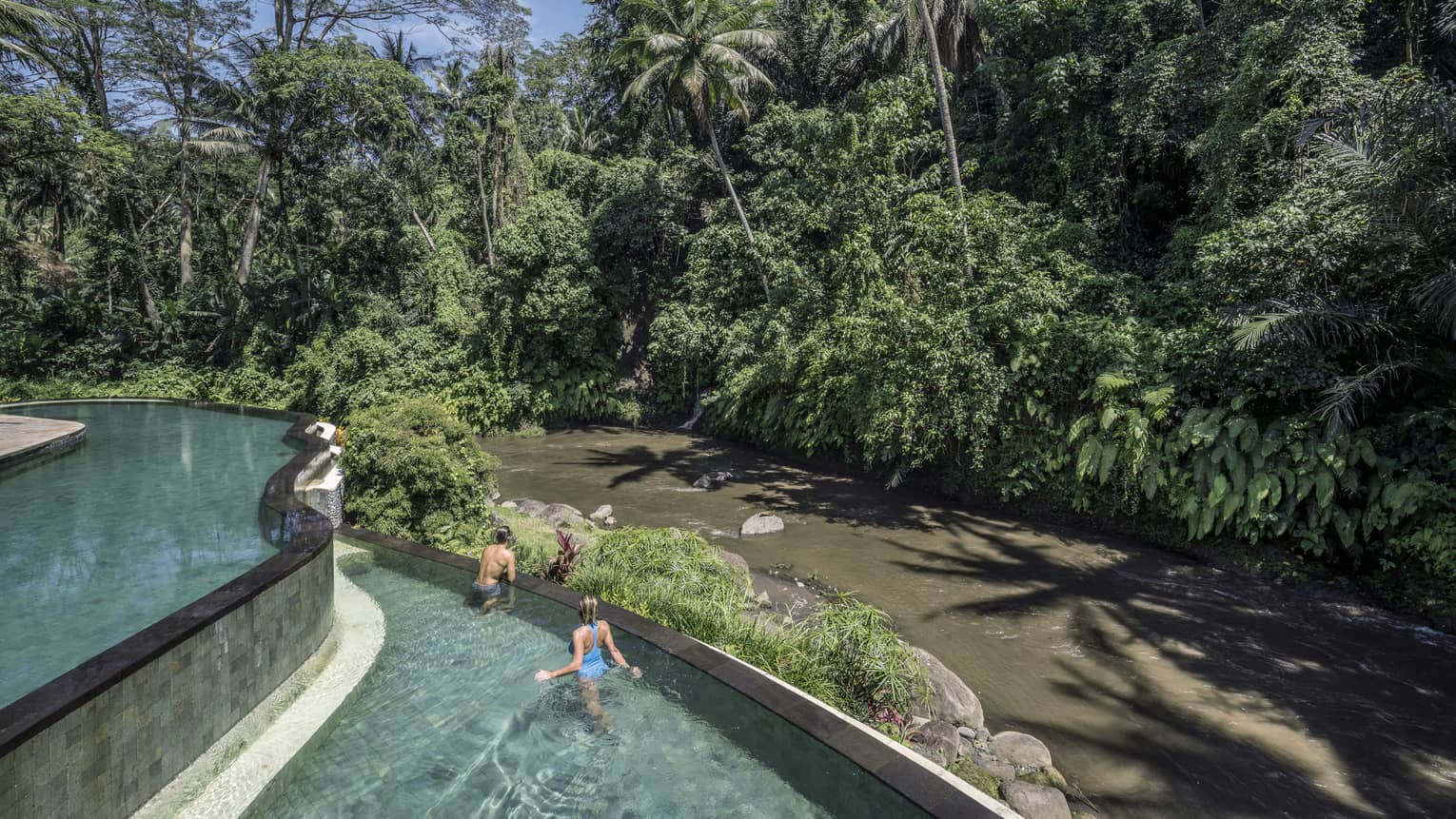 Hotel guests swimming in a pool, overlooking a river in Bali
