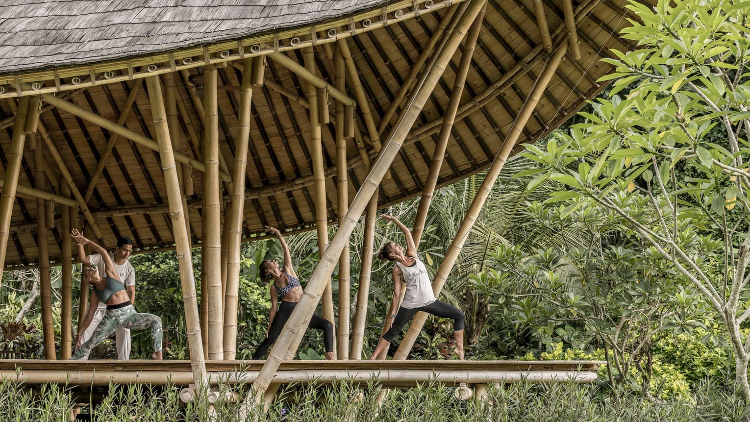Guests reaching towards the sky while participating in an outdoor yoga class in Bali