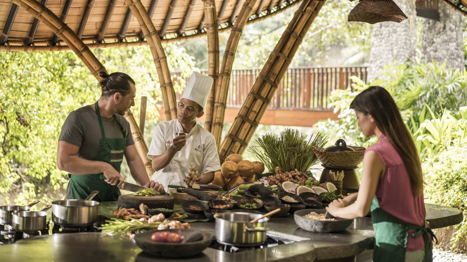 A four season chef instruction a man and woman how to cook in an outdoor kitchen