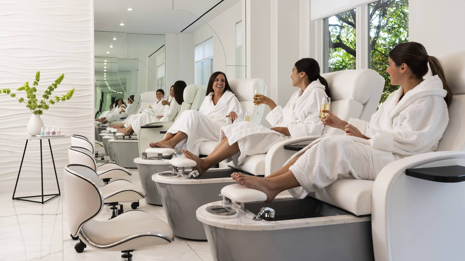 Three women wearing Four Seasons spa robes, sit on pedicure, massage chairs and chat amongst themselves