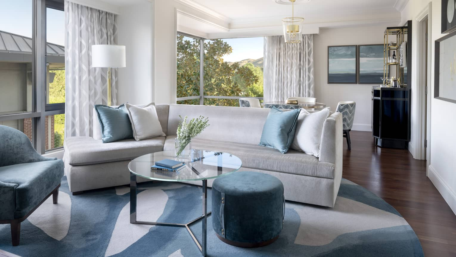 Silver couch with blue pillows, a blue chair, glass coffee table, and a view of trees