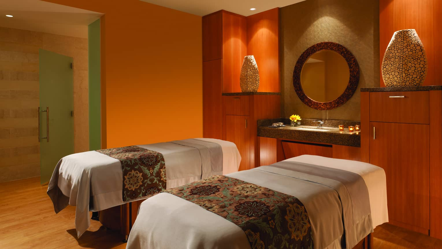 Candle-lit Couples Massage Suite beds with textiles side-by-side in spa