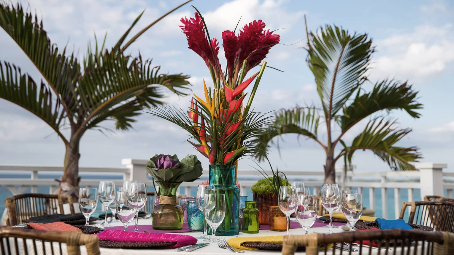 Brightly colored place settings and flowers adorn a a table, outside beside palm trees
