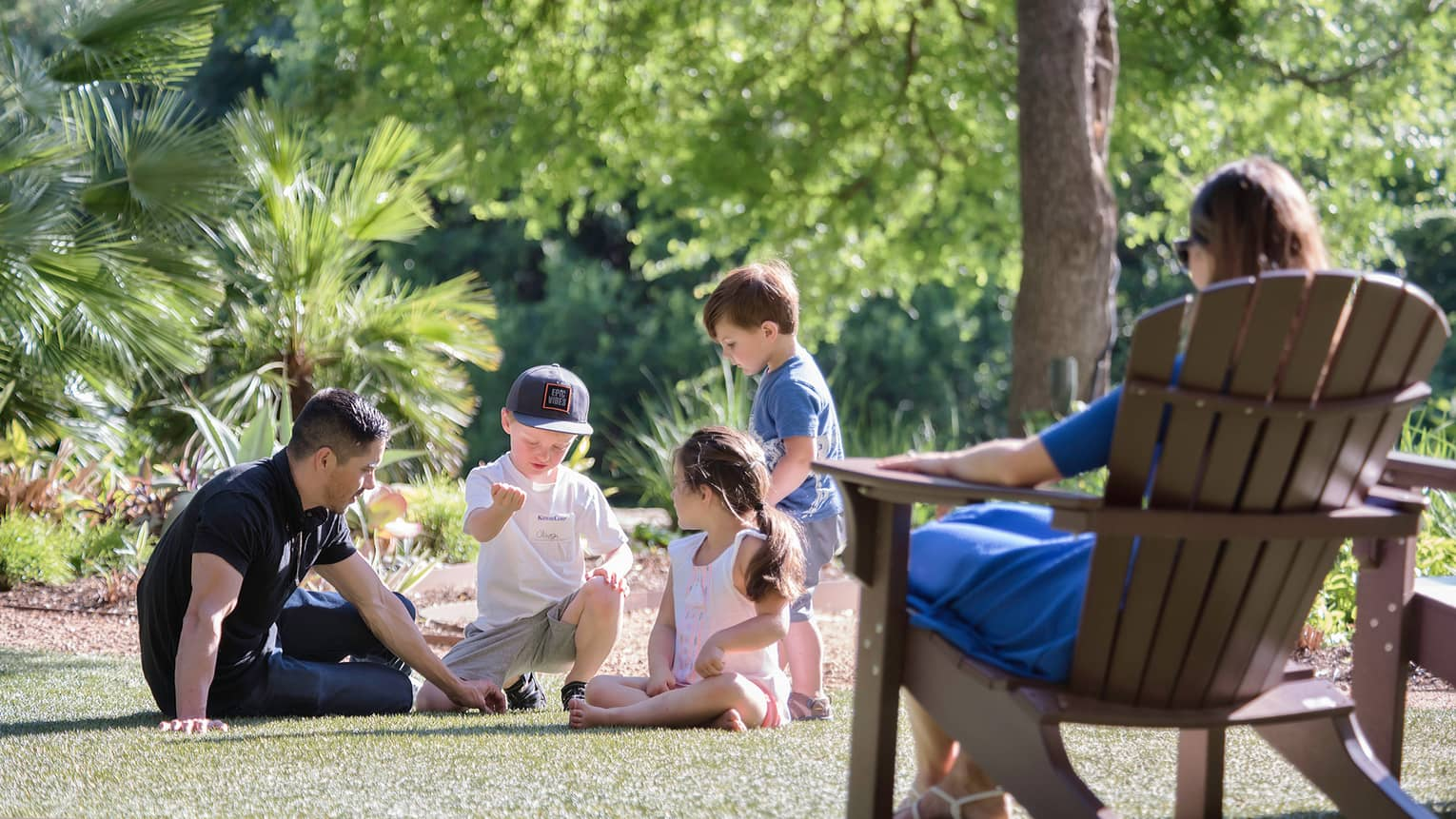 Hotel staff plays game with young children on lawn as woman in deck chair looks on