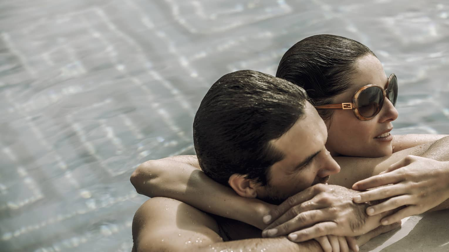 A woman wraps her arm around a man's shoulders as they lean against the side of the pool and gaze into the distance