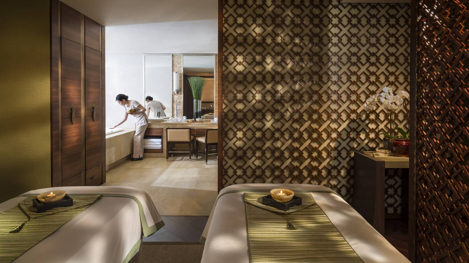 Couples massage beds side-by-side in spa room with candles, wood detail wall, staff preparing bath