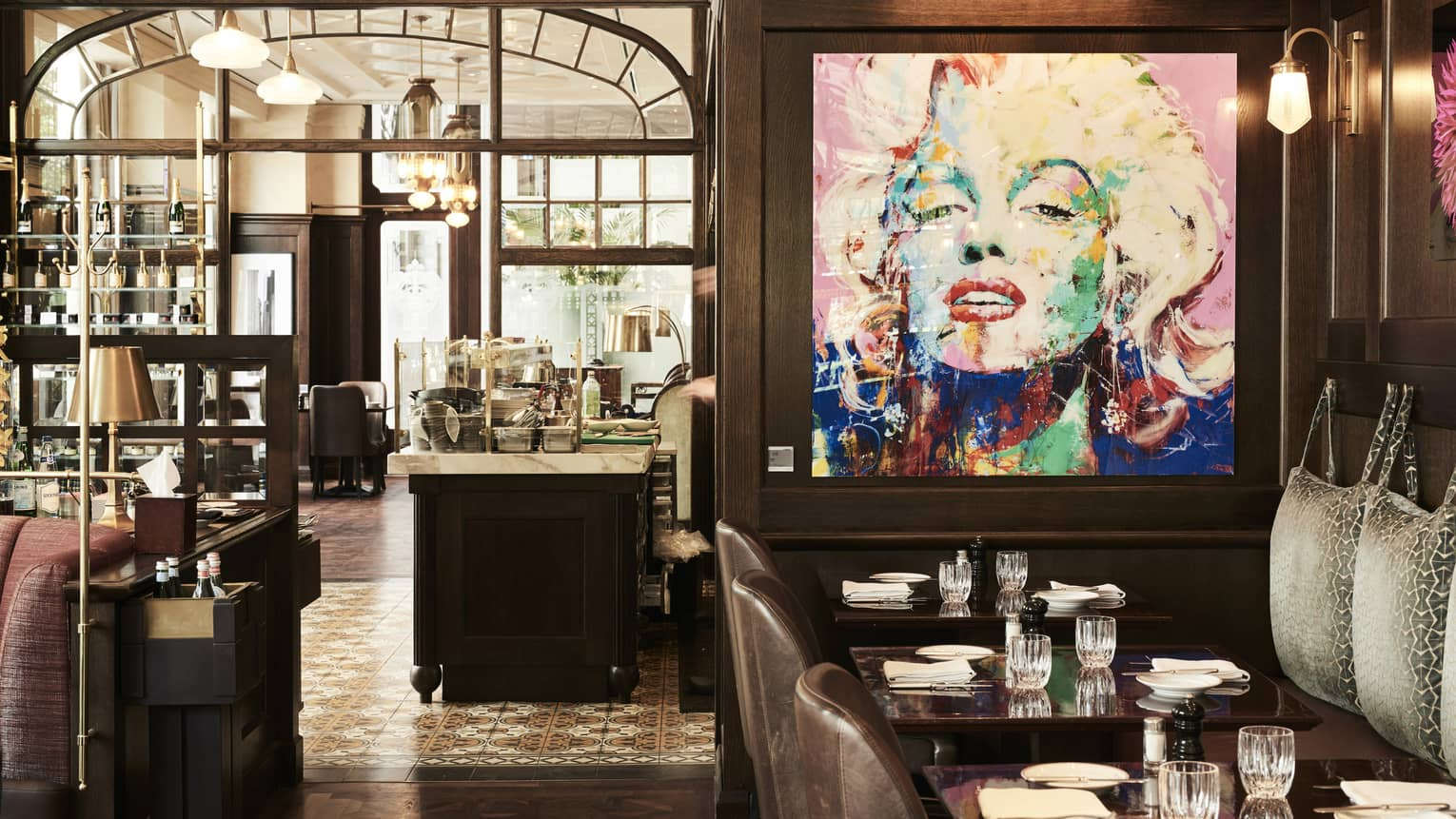 Tables in contemporary brasserie with large artwork of Marilyn Monroe
