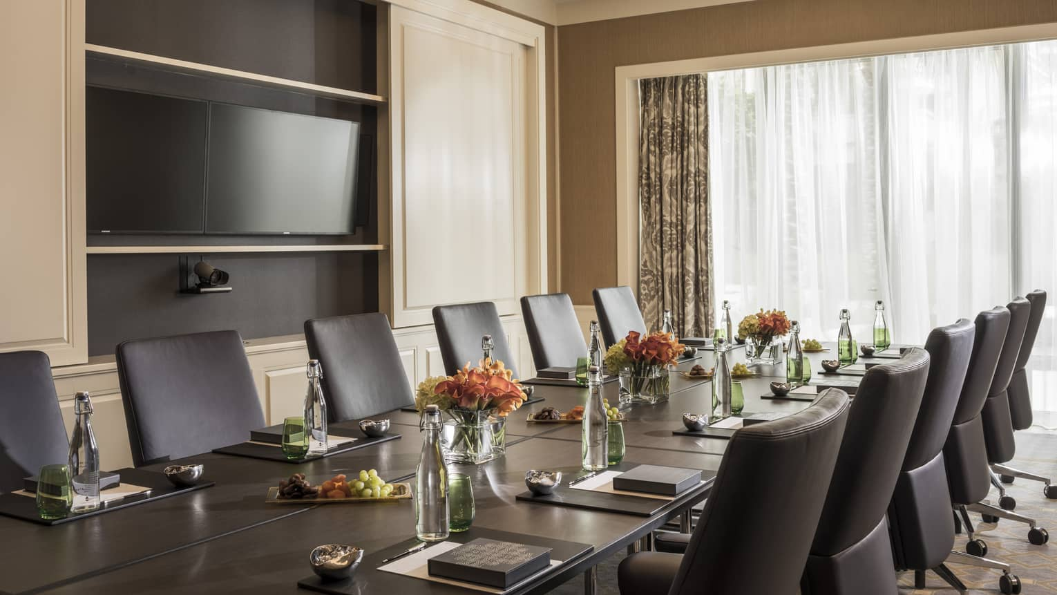 Long boardroom table set with glass bottles of water, flowers in bright meeting room