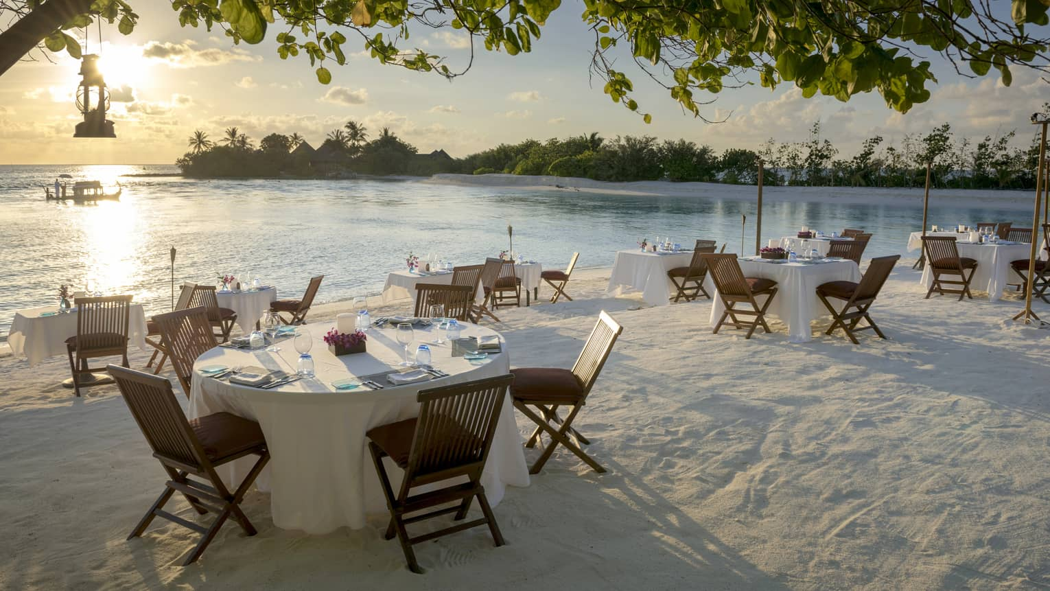 Tables set for dinner with wooden chairs on white sand by ocean shore