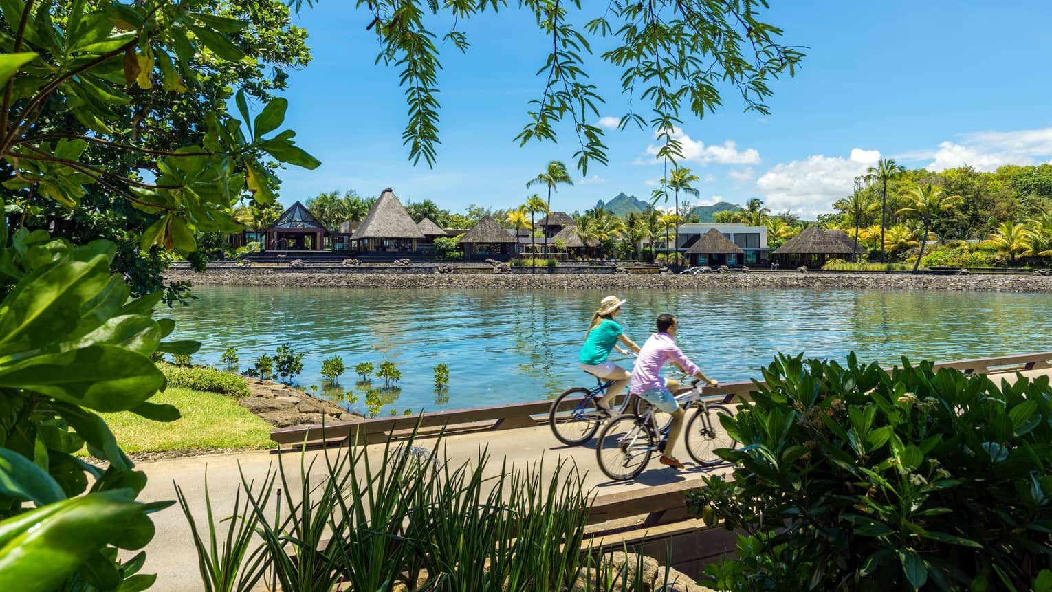 Two guests ride bicycles on bridge over water by resort