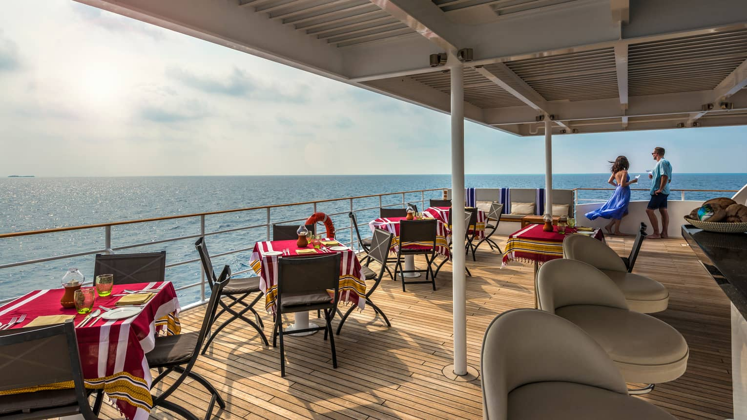 Dining tables, chairs with red tablecloths along covered Island Explorer deck