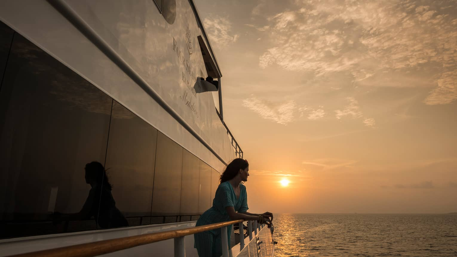 Woman stands at side of catamaran, looks out over water at sunset