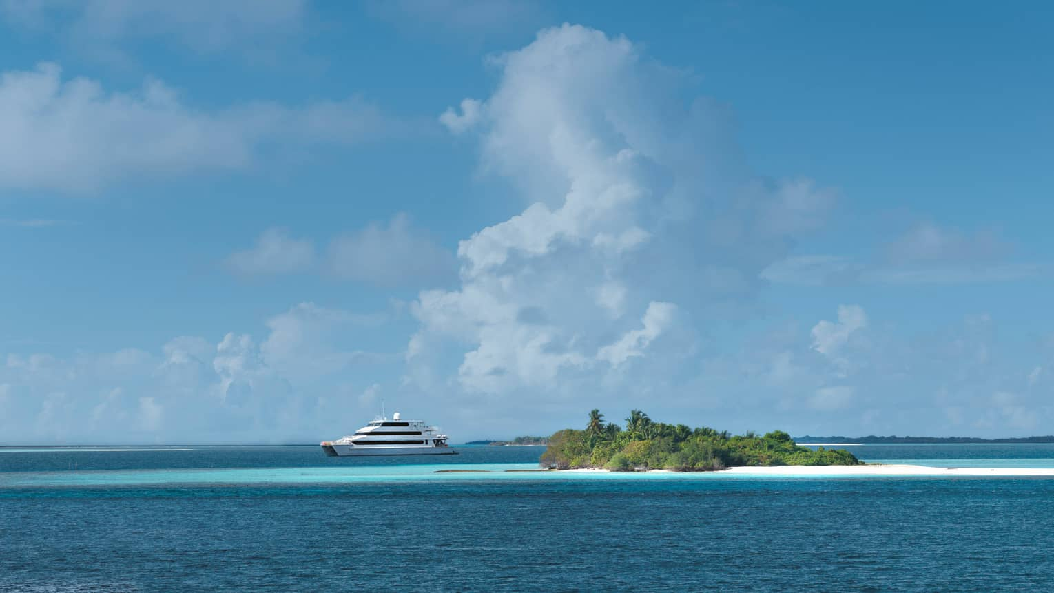 Large white catamaran yacht by small island in ocean