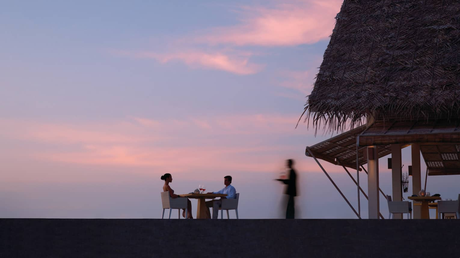 Silhouette of server walking towards couple dining at table near thatched-roof pavilion, pink sunset