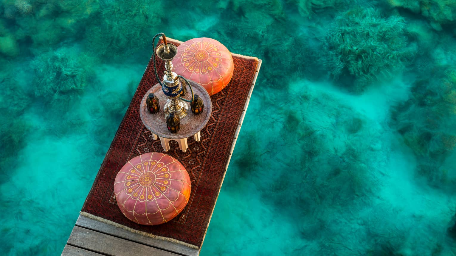 Aerial view of shisha pipe, two round cushions, red carpet on dock over turquoise lagoon