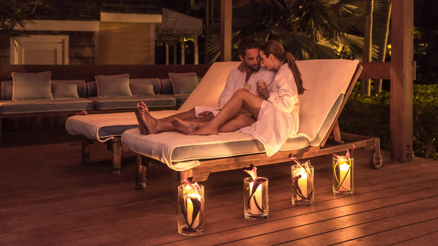 Man and woman in bathrobes relax on lounge chairs, glowing candles on deck at night