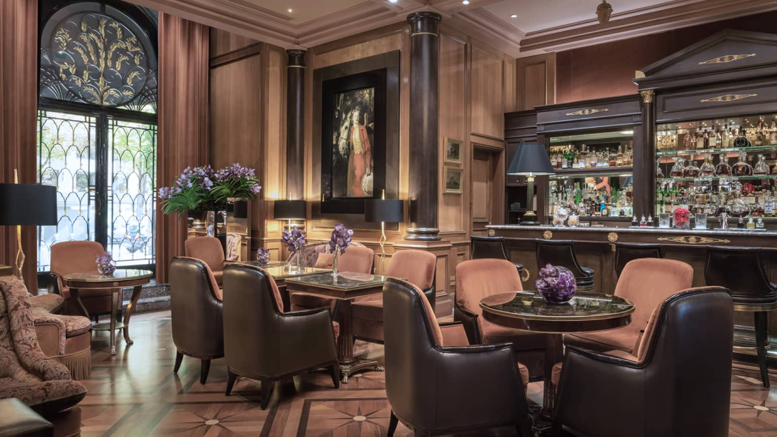 Bar with brown leather barstools and lounge area with rust-colored club-style seating, black lamps and purple flower arrangements