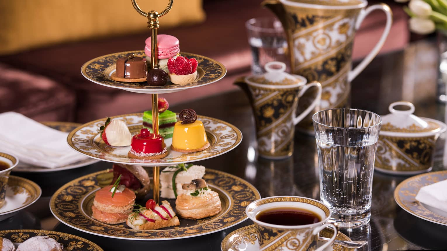 Arabesque High Tea tiered tray with small fancy desserts and finger sandwiches, teapot and mugs