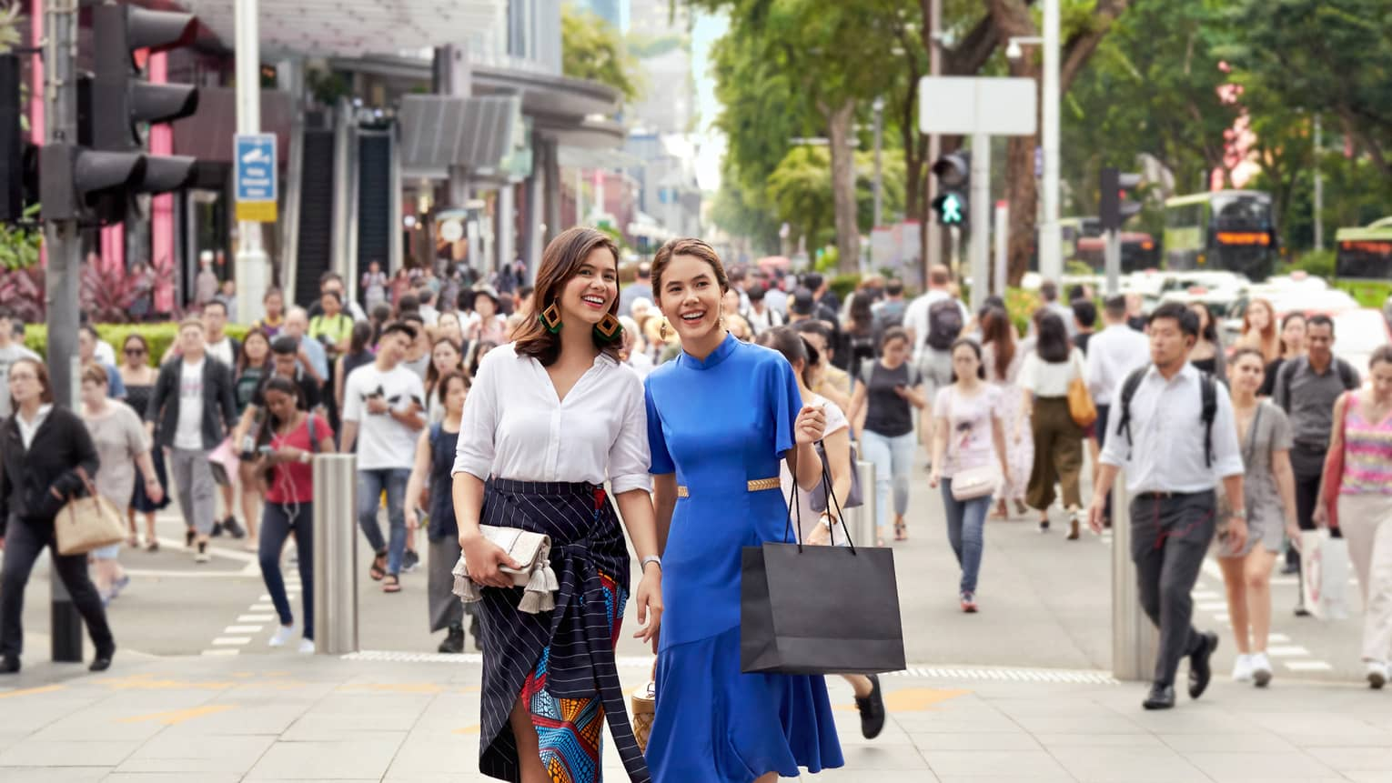 two well-dressed women carrying shopping bags and walking through a busy street in singapore