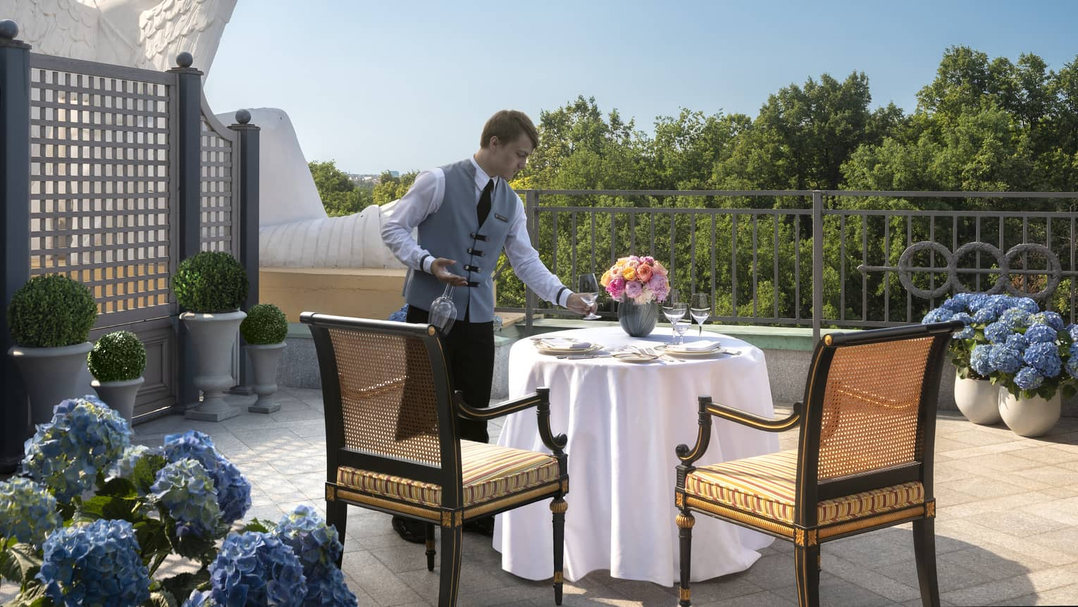 A four seasons staff sets a table for two on the Terrace surrounded by blue hydrangeas