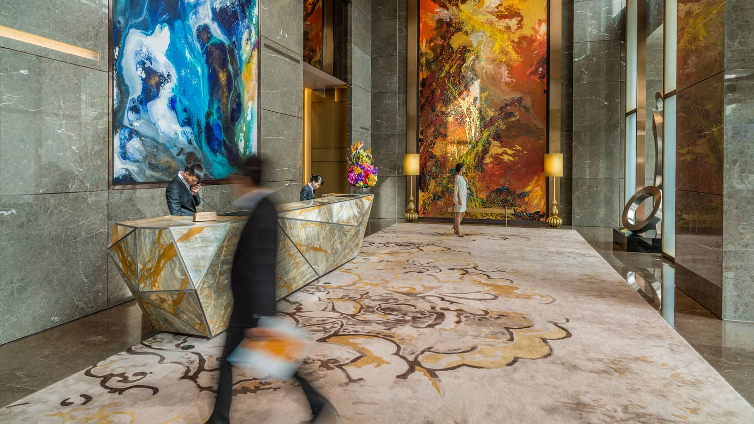 Man wearing suits walks through hotel lobby surrounded by marble, large modern art