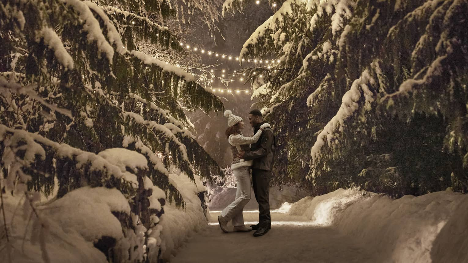 Couple wearing winter coats embrace on snow covered path between large trees at night