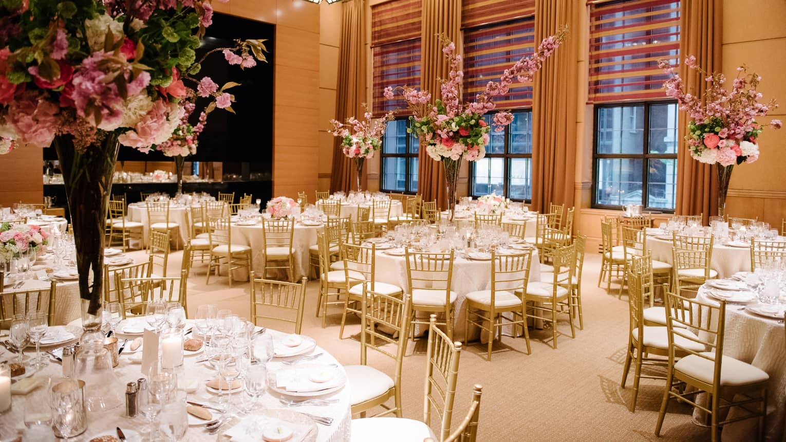 Wedding reception, round tables with gold chairs and large flower centrepieces in tall vases